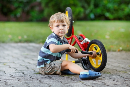 22844770 - little toddler boy repairing his first bike
