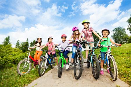 30697550 - happy kids in row wear colorful bike helmets